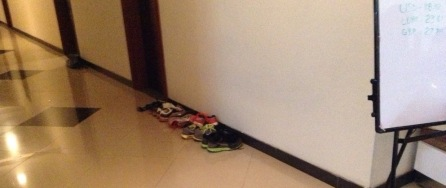 Line of shoes outside an athlete's room