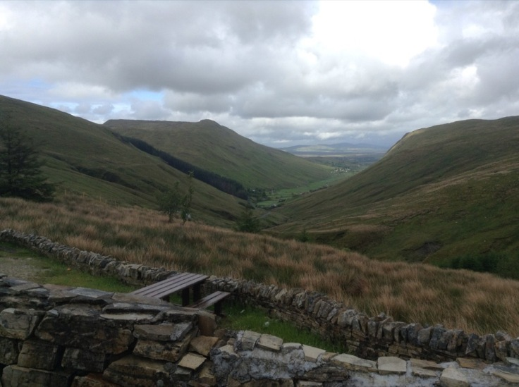 Low wall and picnic table over a green valley with heavy cloud cover