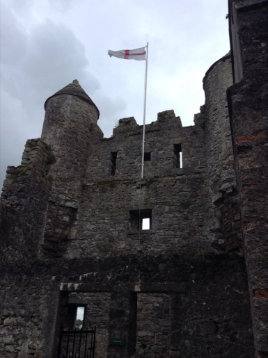 White gate at a castle, NI flag flying above
