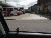 Bus station. Ceramic Froggie looks on from the car.