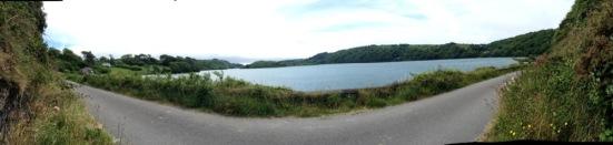 Panorama of road next to a lake