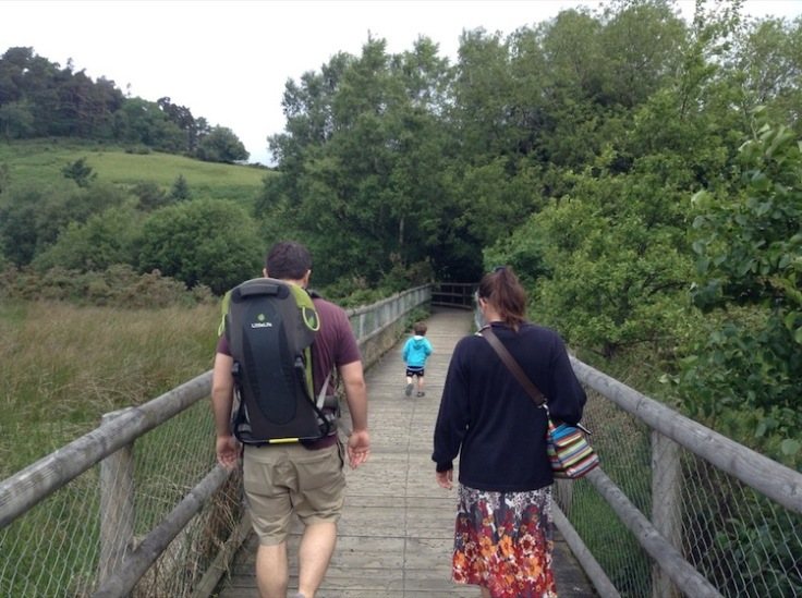 Two adults and one small boy crossing a wooden bridge