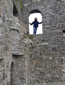 Linda standing in a third/second storey open window in a castle wall