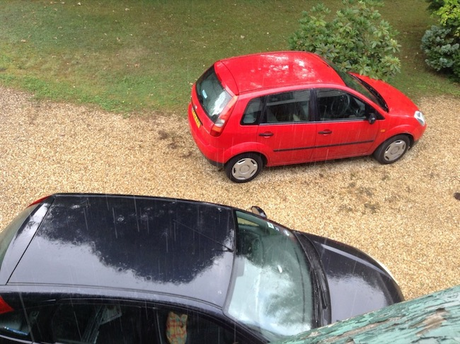 Red fiesta and a black focus, parked on a gravel drive