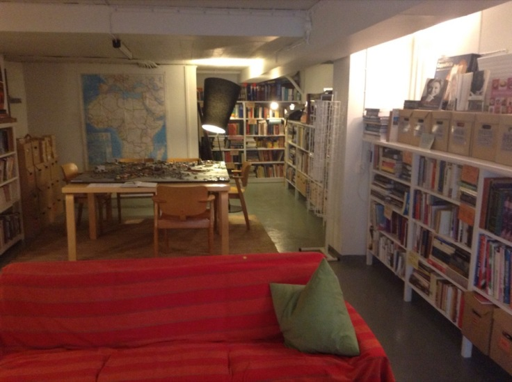Sofa, lamp light, map on the wall, books on shelves all around
