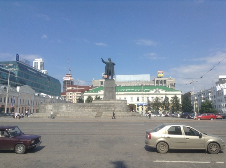Statue of Lenin on a raised platform, in a public square
