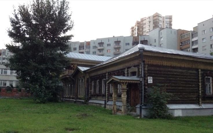 Old wooden house in front of modern apartment blocks