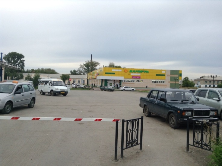 Car park with lada, supermarket behind, a gaudy yellow in colour.