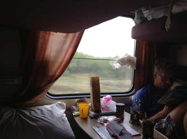 View from train compartment, showing curtains, pillow, table with possessions
