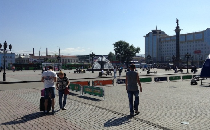 Public square in Krasnoyarsk. A fountain in the middle, rust and grey coloured tiles on the floor