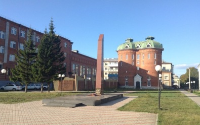 Monument and library at Ilanskaya. Monument is tall and thin, ending with a sloped roof. The library has a twin towers look, with a copper-green rounded roof