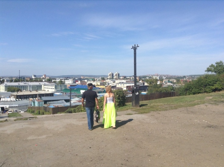 Two people, one in bright green, almost fluorescent, trousers, look over the city.