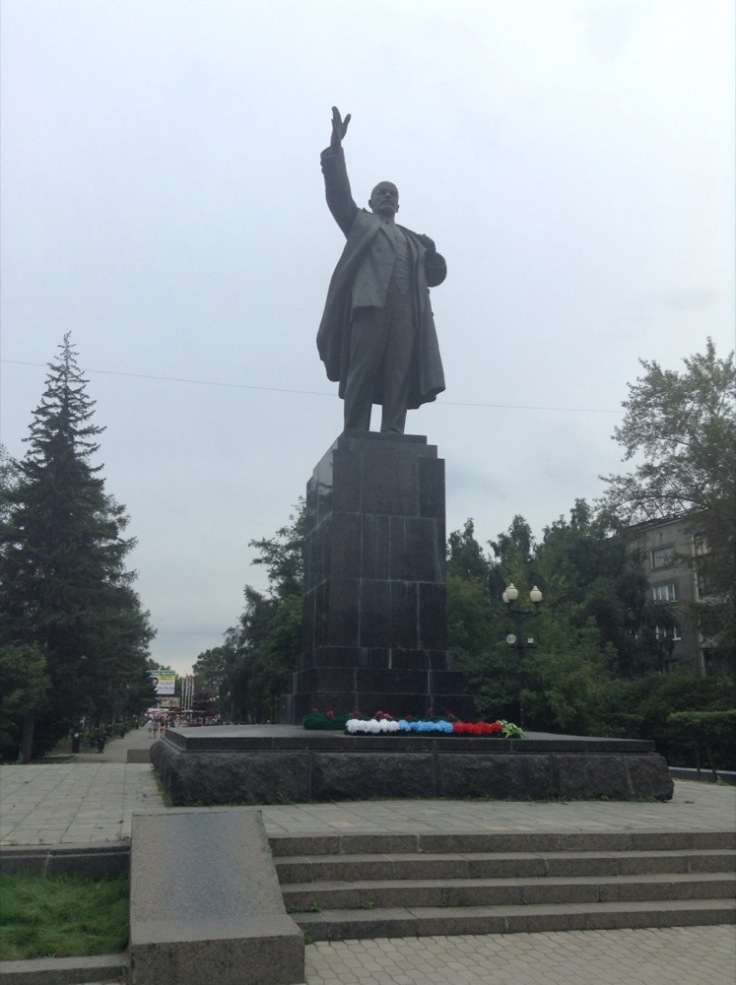 Statue of Lenin on a plinth, with one arm raised to the sky. A few flowers tidily decorate the bottom.