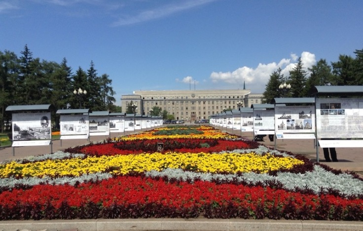Colourful floral display in the centre of a boulevard. Information boards on both side and the grand admin building is at the end