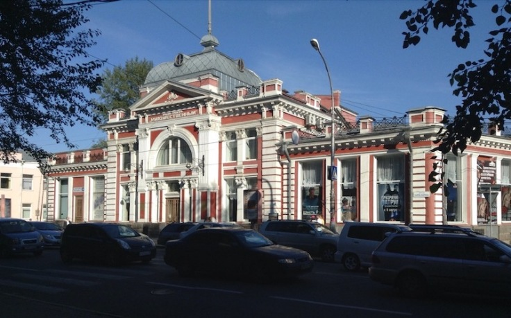 Ornately decorated cinema building, in bright sunshine, while all the cars outside are entirely in shade