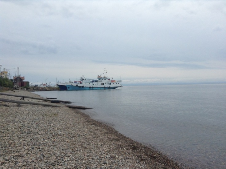 Lake Baikal. The shore is pebbled. A couple of large boats wait a few hundred metres away