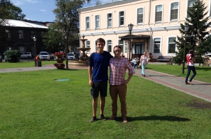 Two men on the grass in a small public square