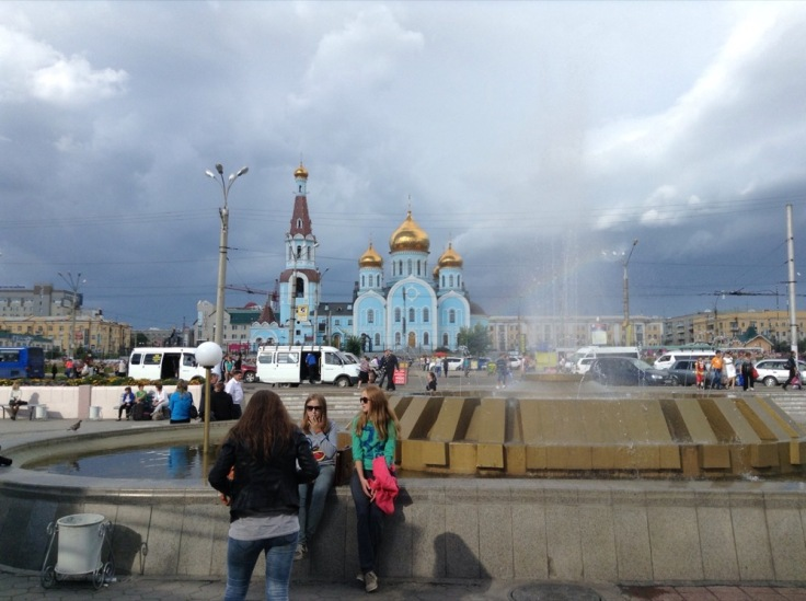 Public square in Chita. Three girls stand in front of a pool. A blue church is at the far end