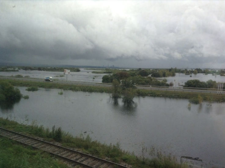 A flooded landscape, with a road and train tracks above it
