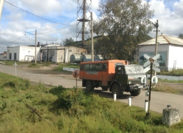 An old Soviet-looking truck waits at a railway crossing, industrial buildings behind