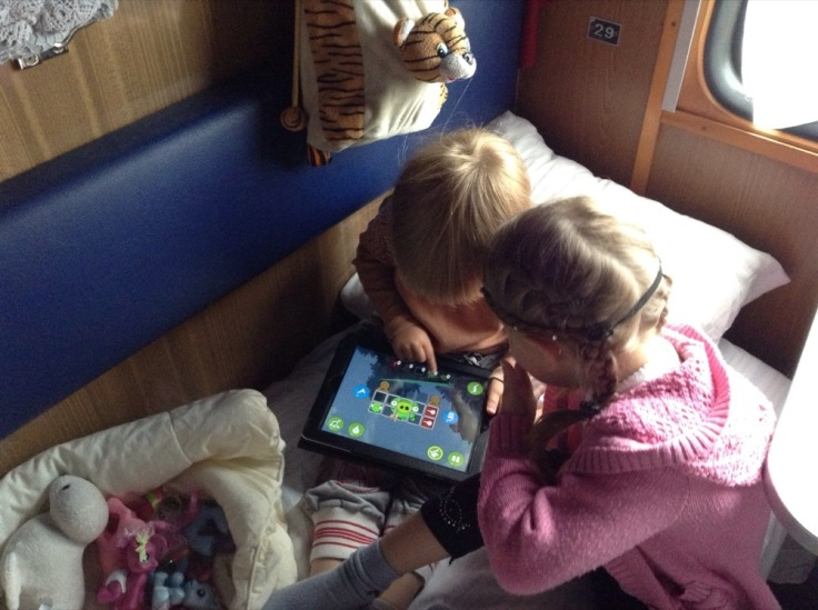 Two children playing on the iPad in a train compartment
