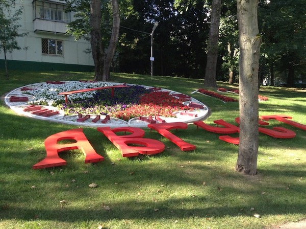 Russian lettering round a large-scale, person-sized clock on the grass