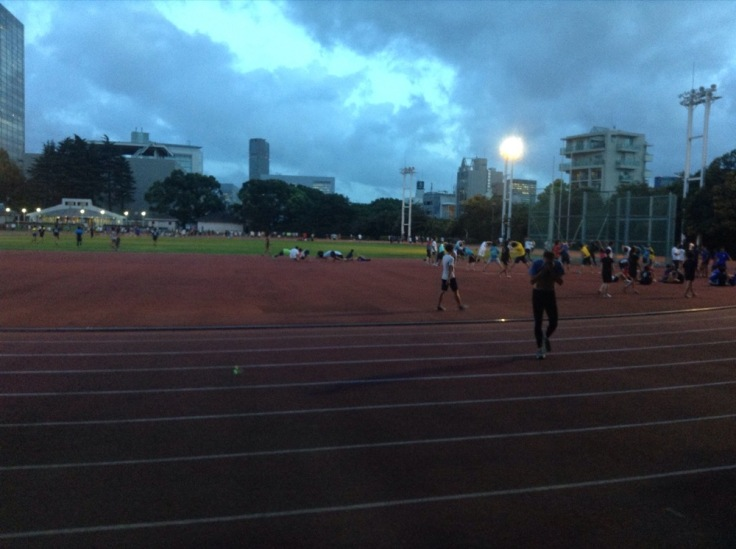 A busy running track. Lots of people on the grass and exercising in the centre.