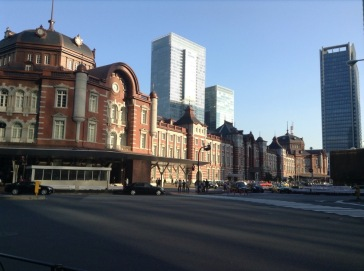 Older architecture of Tokyo Station, with modern skyscrapers rising behind