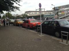 Parked taxis; black, red, yellow, in a row