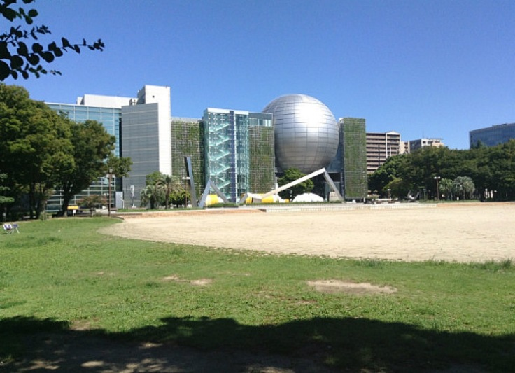 Sandy plot in front of the large sphere and glass-fronted buildings that make up the museum