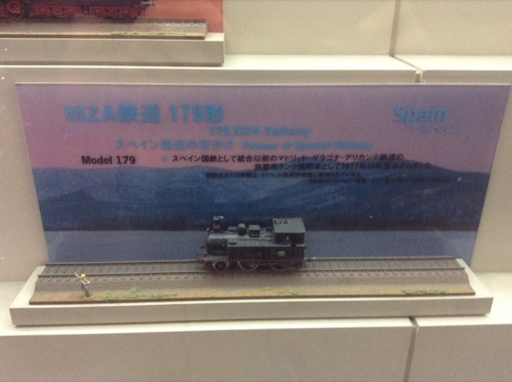 A small model train, with the word 'Spain' printed behind