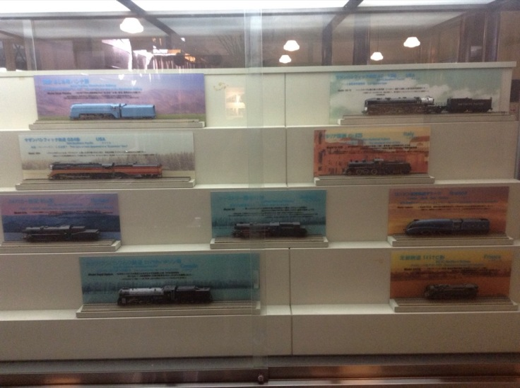 Model trains, each on it's own coloured display stand