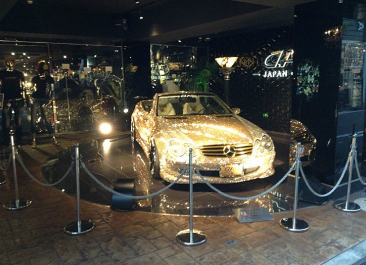 A golden car. Blinged up Mercedes.