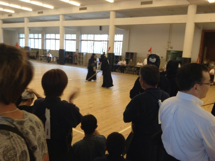 In a gym, two people practice Kendo, dressed all in black, while others watch
