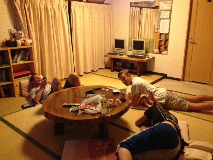 Three people chatting, lying on mats on the floor of a Tokyo hostel