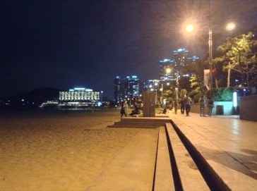 Beach to the left, promenade right. Buildings lit up behind