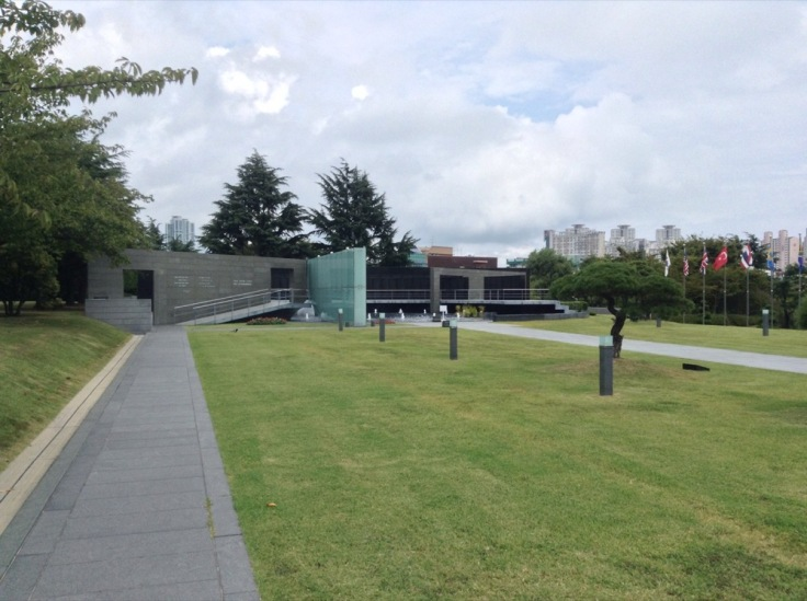 UN Memorial Cemetery; grass and modern building.