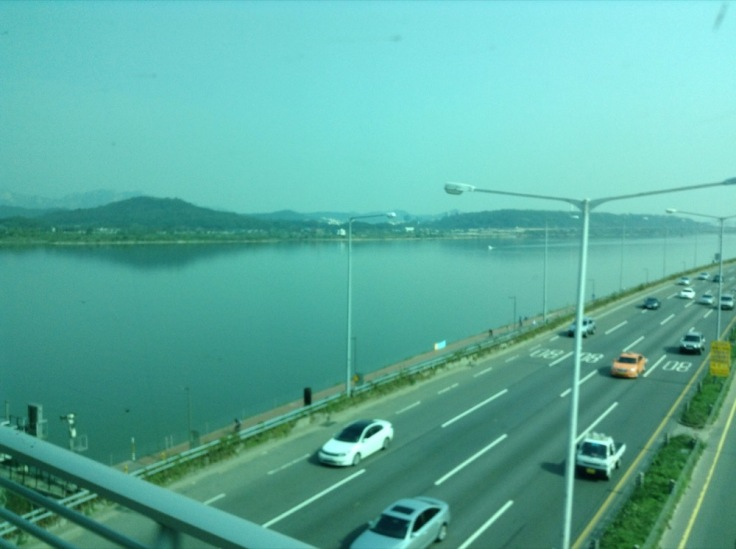 Busy highway next to water, which has mountains on the far side