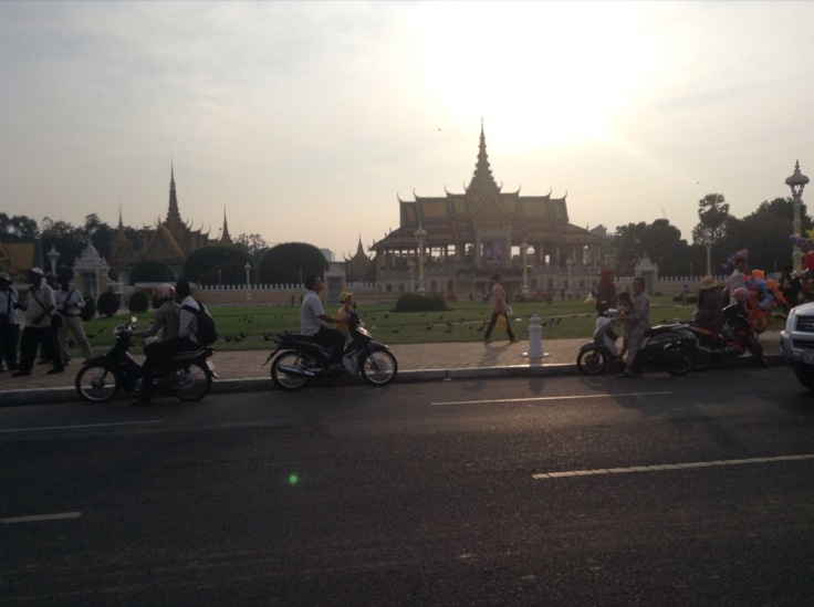 Motorcycles roll past the elaborate pagoda of the Royal Palace