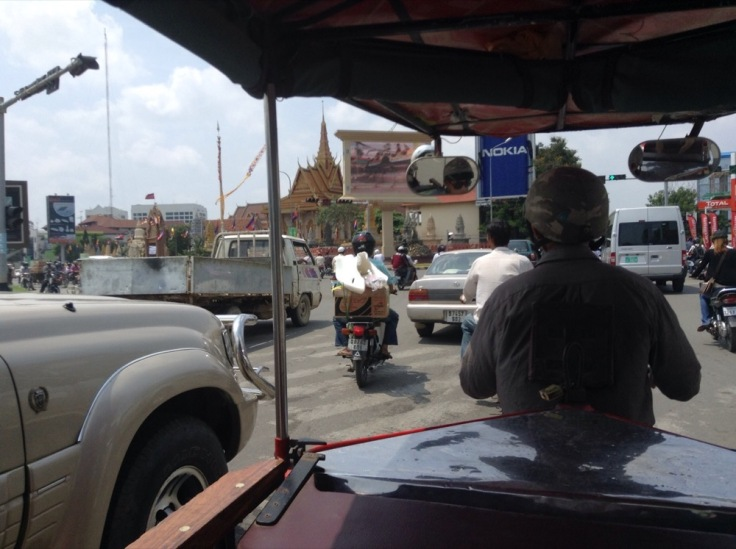 View from the back of a rickshaw, traffic all around and a temple off to the left