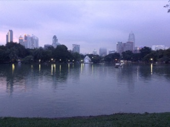 Large body of water in the park, with skyscrapers rising in the distance, behind
