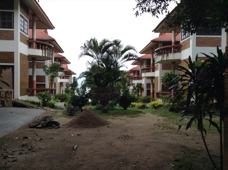 A pile of earth in the middle. A palm tree, and resort buildings either side, decaying