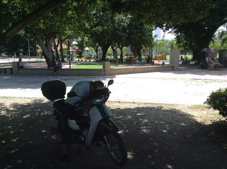 A man leans forward, sleeping on his moped, in the shade