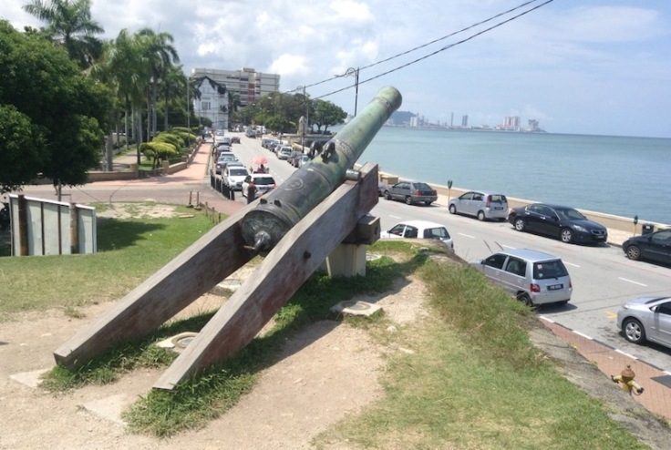 A large, gree cannon points out to sea
