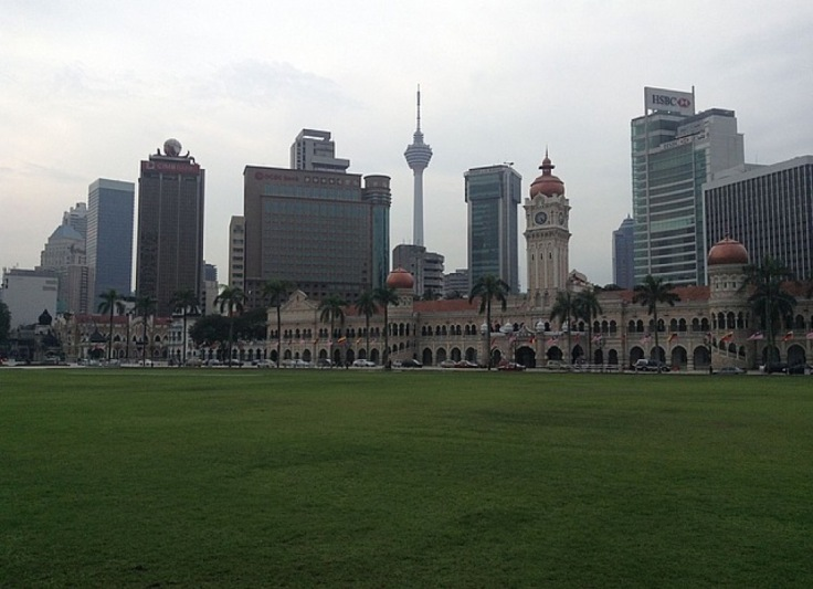 A view of the skyline, from the cricket pitch. A magnificent pavilion is on one side of the green. KL Tower away in the distance.