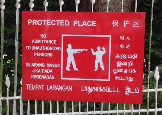 Sign saying protected place, no admittance, with a silhouetted man with hands up, as another points a gun at him