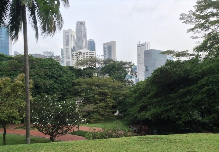 Grassy lawn and a park nearby, with tall skyscrapers behind