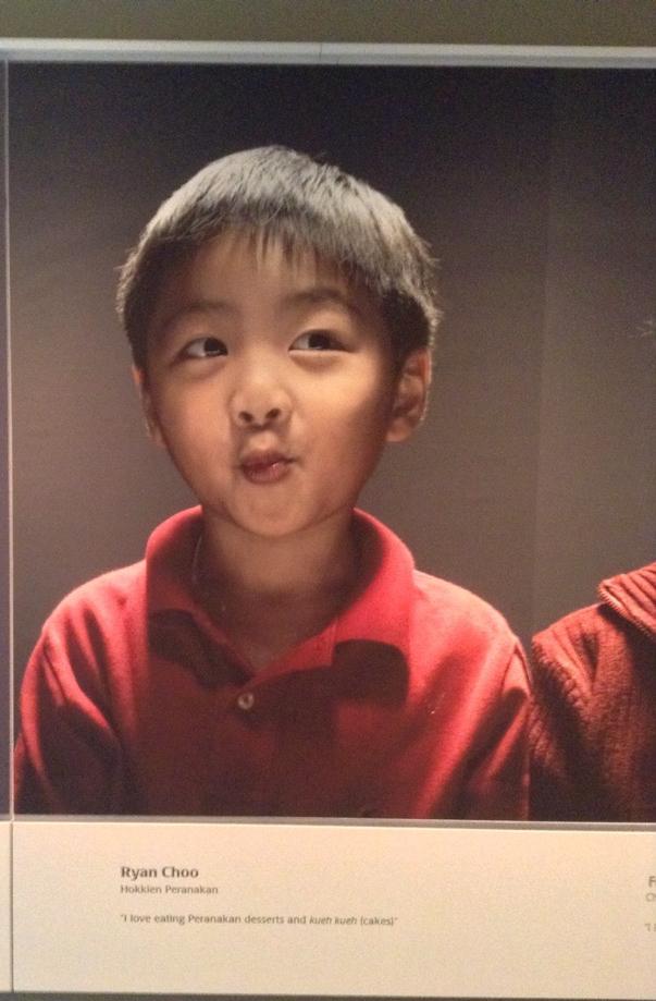 A portrait of a small boy, Ryan Choo, looking cheeky.