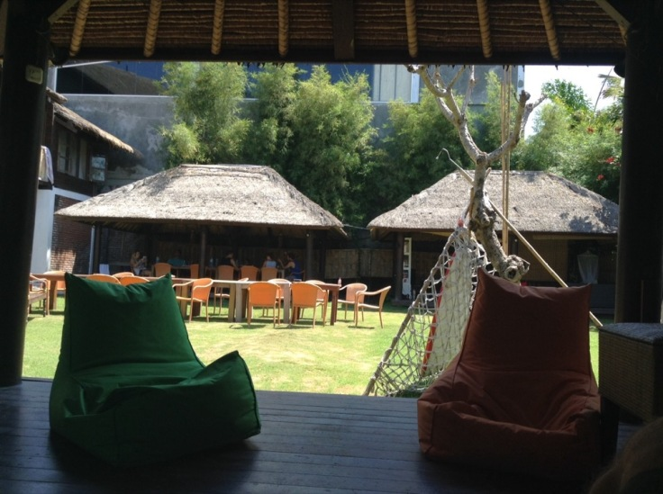 Beanbags in a shaded hut, looking out over sunshine on the grassy courtyard, thatch-covered structures on the other side