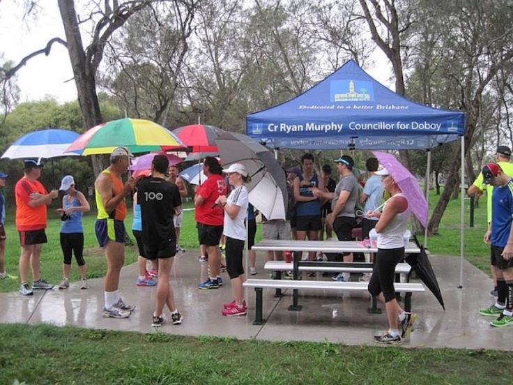 Runners and volunteers gathered under a gazebo and umbrellas as the rain falls